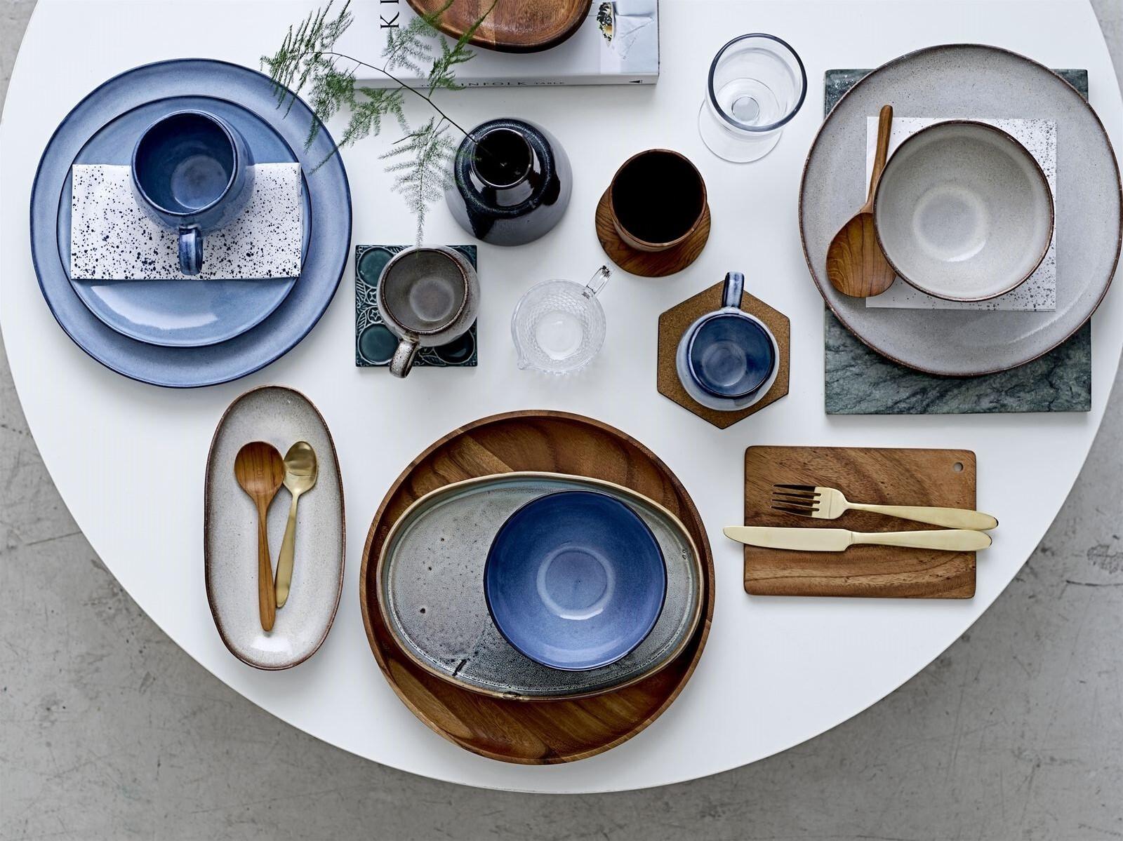 Prostřený stůl s různými druhy nádobí a příborů